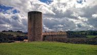 Contrast: Torre de planta circular adossada a la masia de cal Cortès. La torre podria haver estat construïda durant la primeria del segle XIII. Consta de tres nivells separats per voltes cupulars de pedra.  Ramon Sunyer